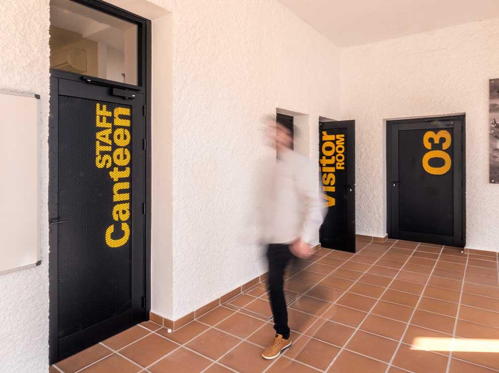 Diseño de señalética amarilla para puertas.